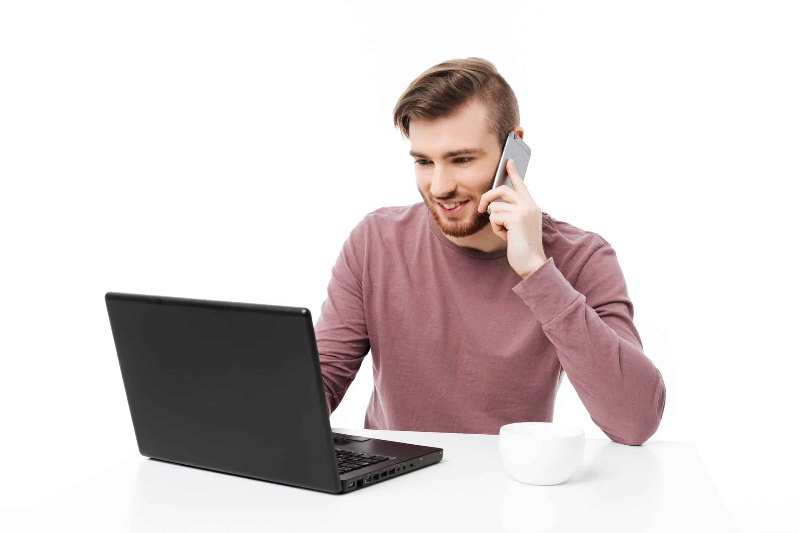 Handsome young bearded man working at the laptop computer talking on the phone and looking at the display isolated