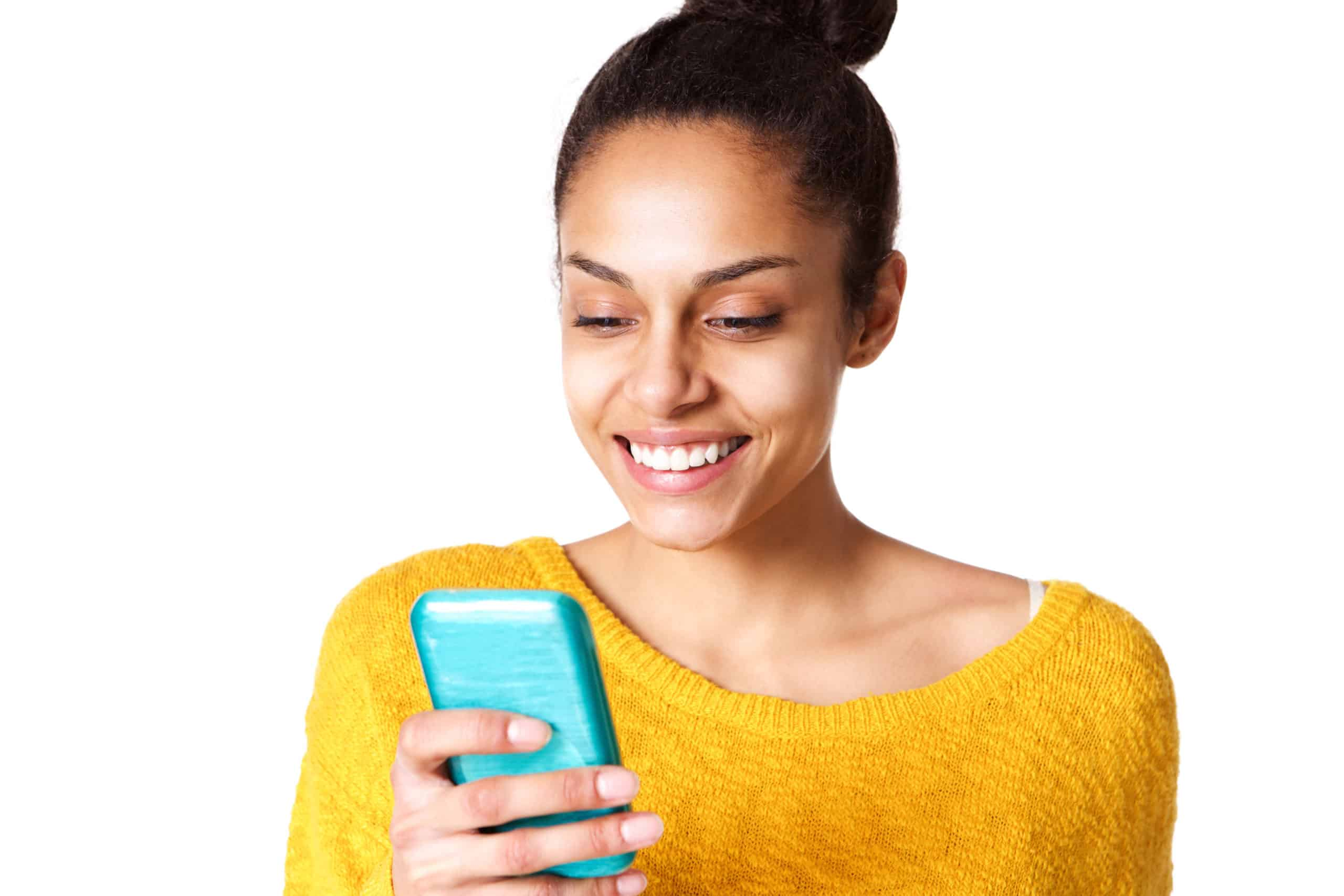 Close up portrait of happy young african woman reading text message on mobile phone against white background